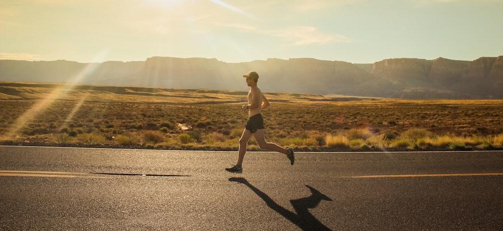 man in black shorts running on gray asphalt road during daytime