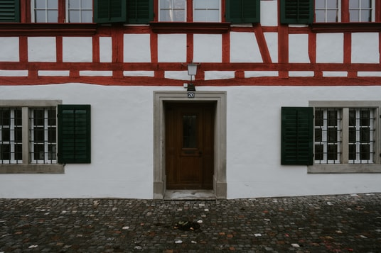 brown wooden door on white and red concrete building