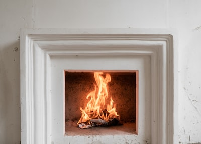 white wooden framed fire on gray concrete floor fireplace teams background