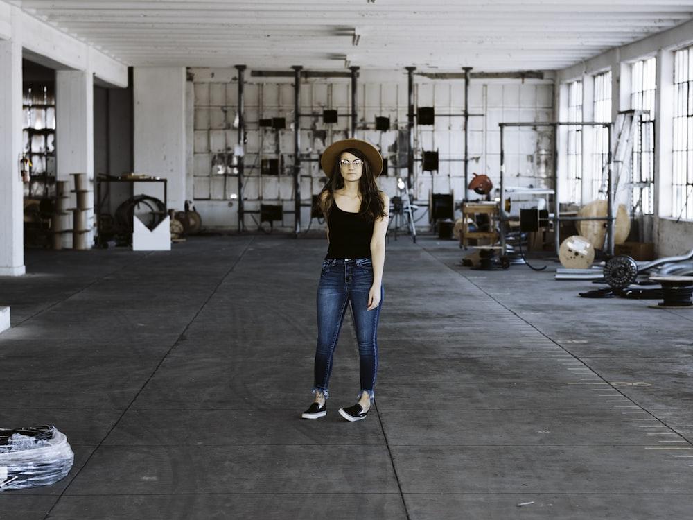 woman in blue denim jeans standing on gray floor tiles