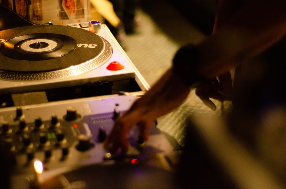 person playing black and white dj controller