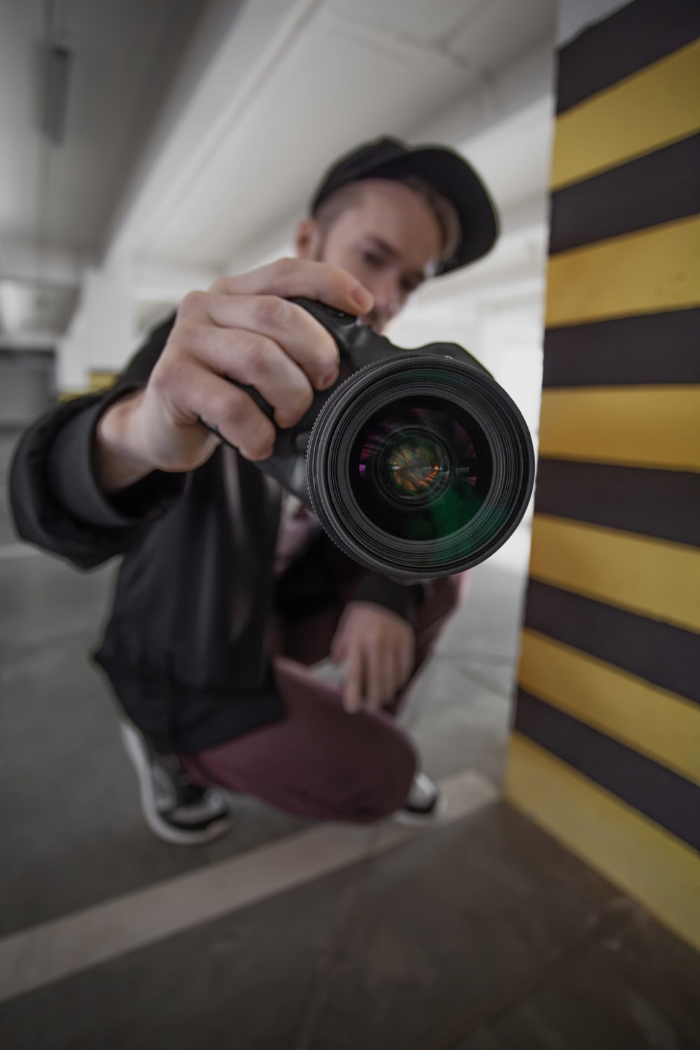 man in black and yellow striped long sleeve shirt holding black camera lens