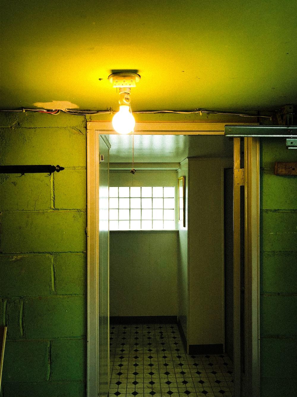 white pendant lamp turned on near white wooden door