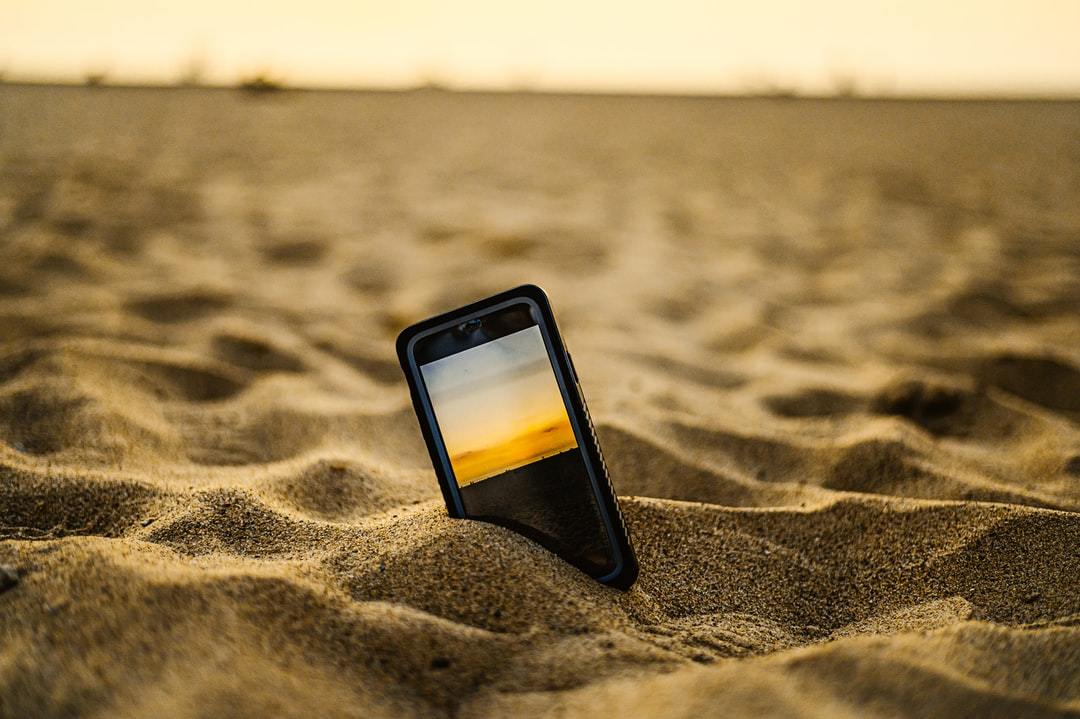 Iphone 11 In Sand Taking A Picture of the Sunset - unsplash