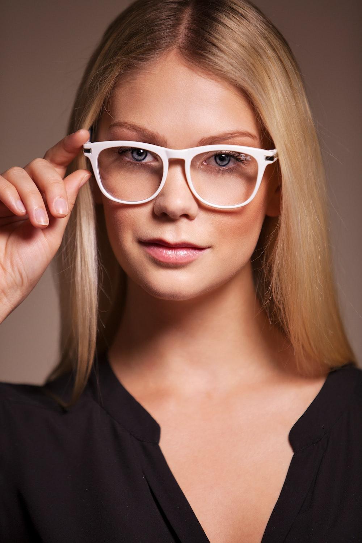 woman in black shirt wearing white framed eyeglasses