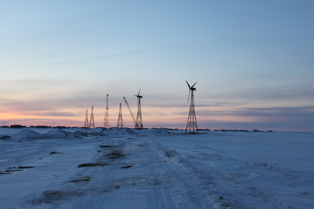 wind turbines on snow covered field during sunset