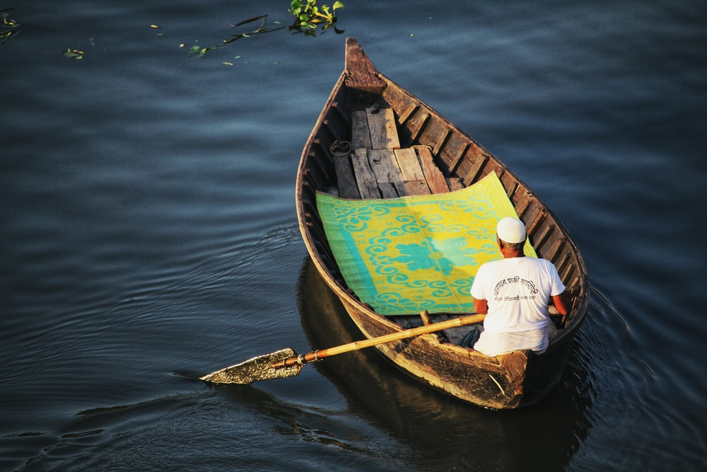 man in white shirt and black pants riding red and yellow boat on blue water during