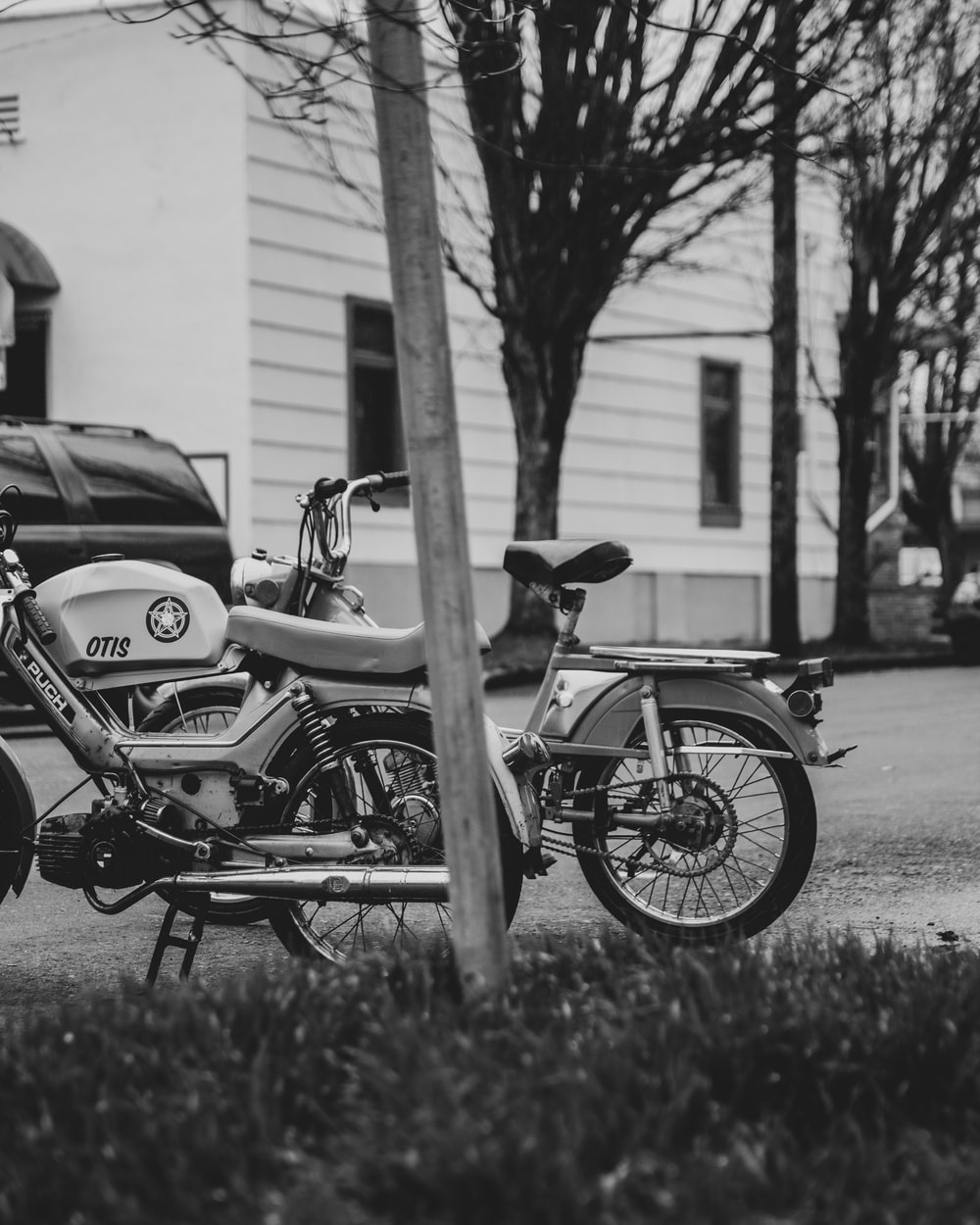 grayscale photo of motorcycle parked beside road