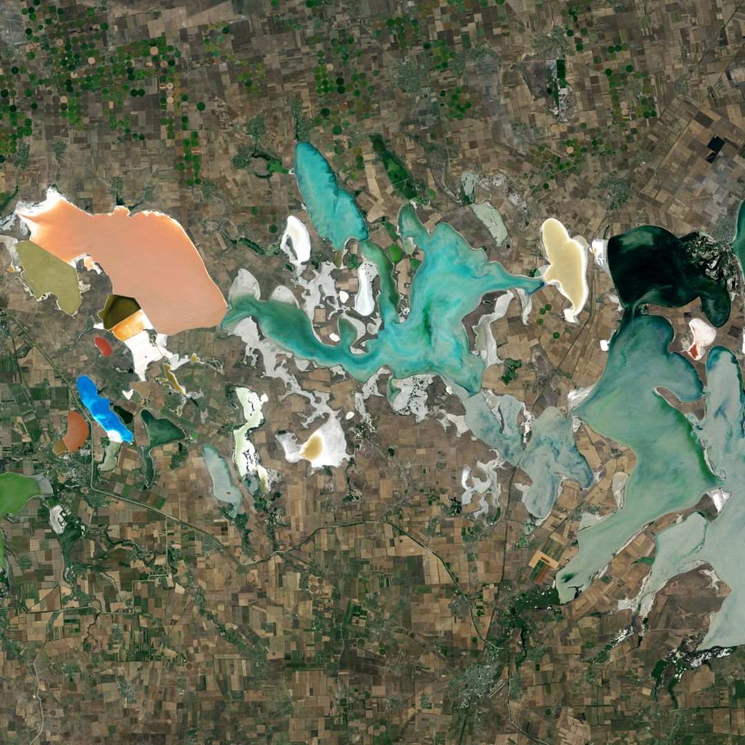 """Varied types of microalgae flourish in this colorful network of shallow, salty lagoons at the neck of the Crimean Peninsula between the Black Sea and the Sea of Azov. This natural color image portrays the unnaturally strange colors of the area known as Sivash, which is nicknamed the """"putrid sea"""" because the algae in some of the lagoons produce a rotten smell."""