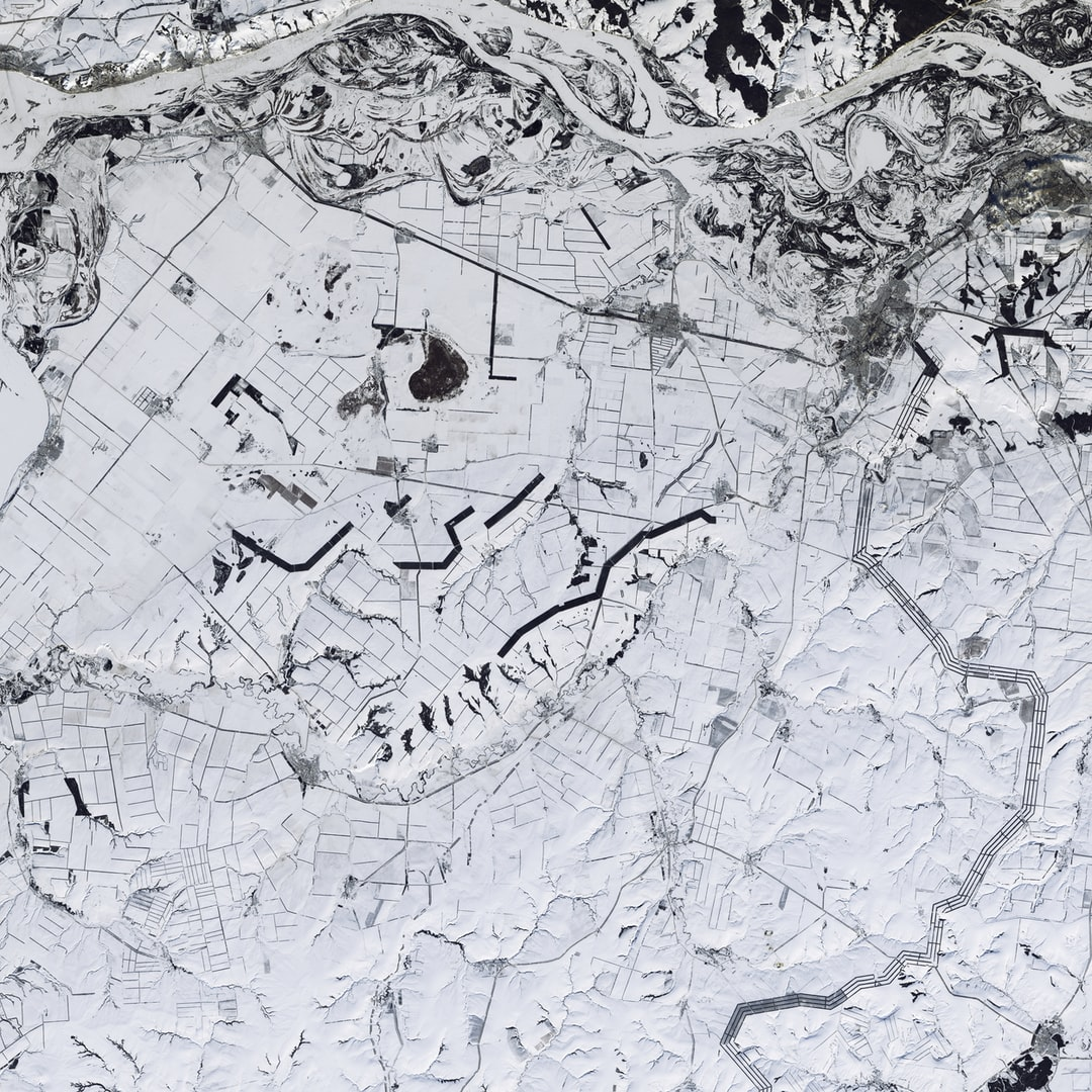 Is this a black-and-white image? No, this is a natural color image of snow-covered southwestern Russia. Windbreaks, roads, and fence lines look like random pencil marks near the Volga River, which flows across the top of the image. The thick lines are trees planted to protect fields from dry wind and erosion; these windbreaks retain snow, allowing more moisture to penetrate into the soil.