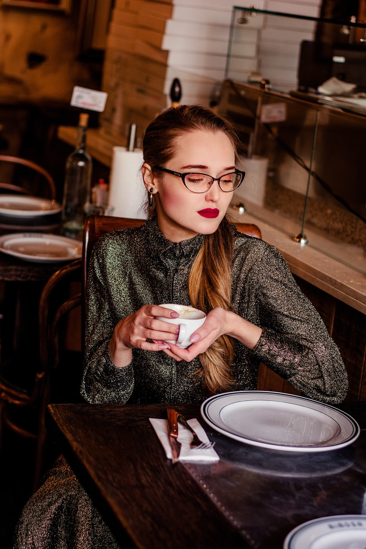 woman in gray sweater holding white ceramic mug
