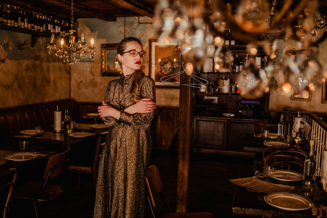 Woman In Brown and White Coat Standing Near Brown Wooden Table - unsplash