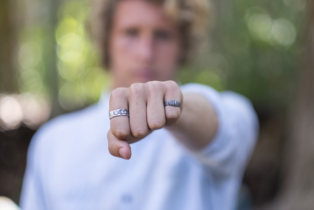 person wearing silver ring in white shirt