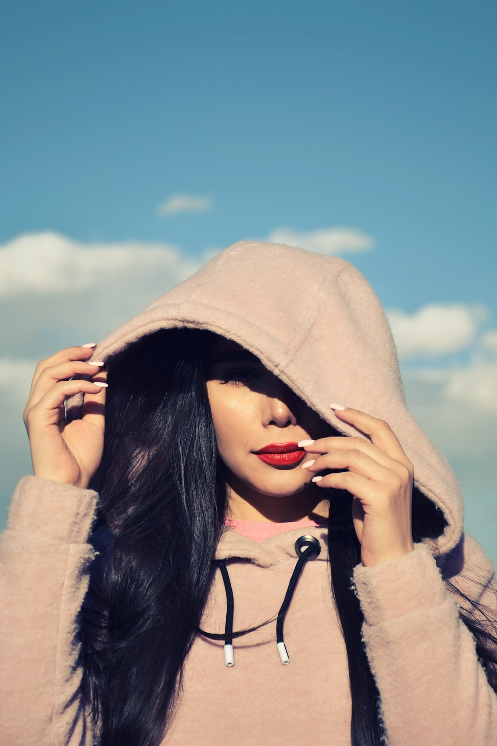 woman in gray hoodie covering her face with her hand