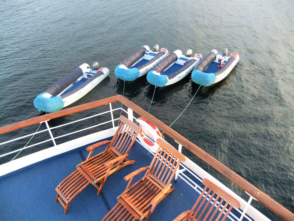 brown wooden chairs on blue and white boat on body of water during daytime