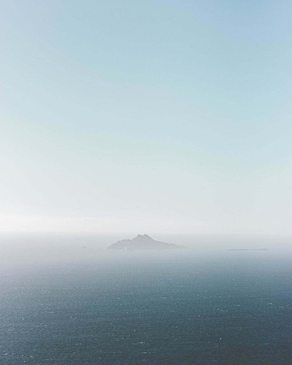 brown mountain on the middle of the sea