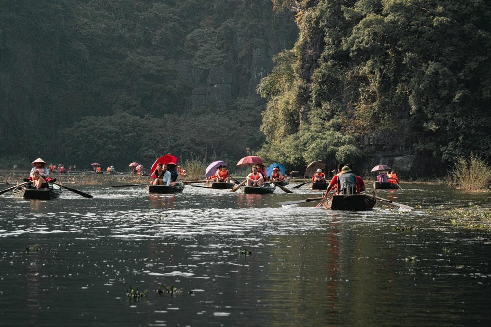 people riding on red kayak on river during daytime