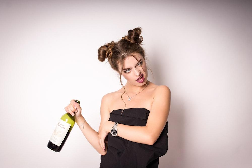 woman in black spaghetti strap top holding green glass bottle