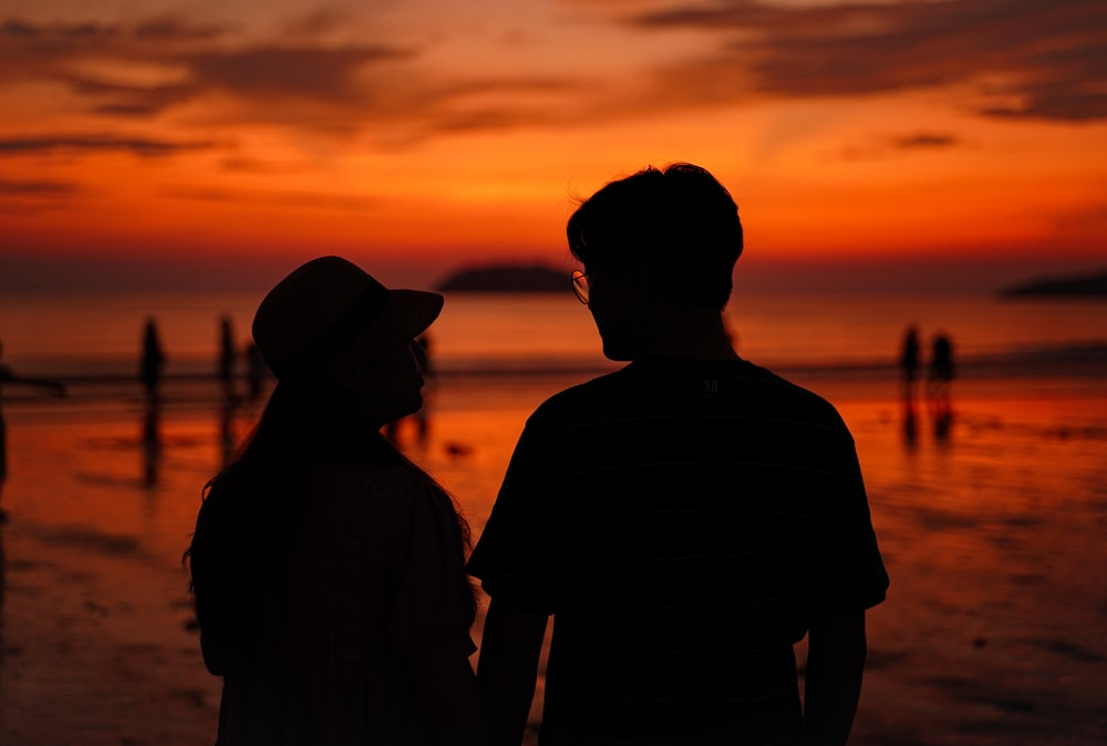 silhouette of 2 men standing during sunset