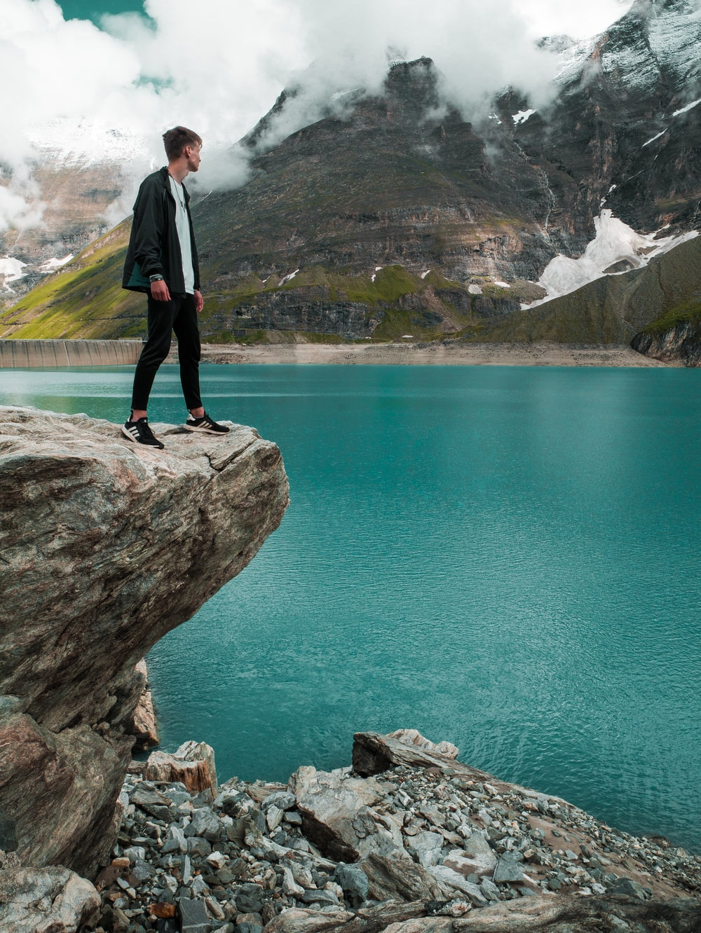 man in black pants standing on rock near body of water during daytime