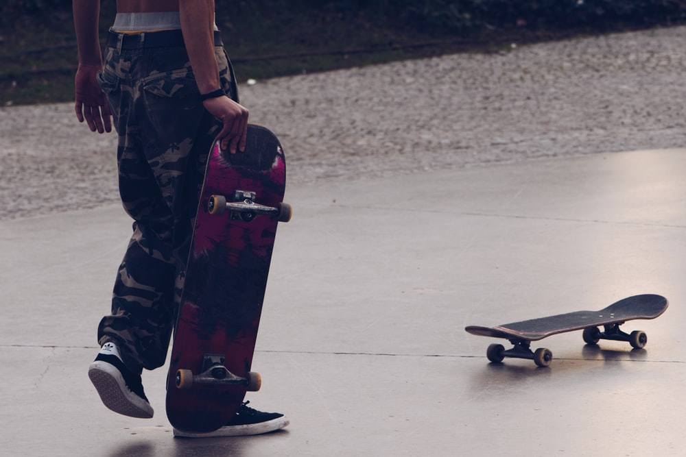 man in green and brown camouflage pants and black shoes holding black skateboard