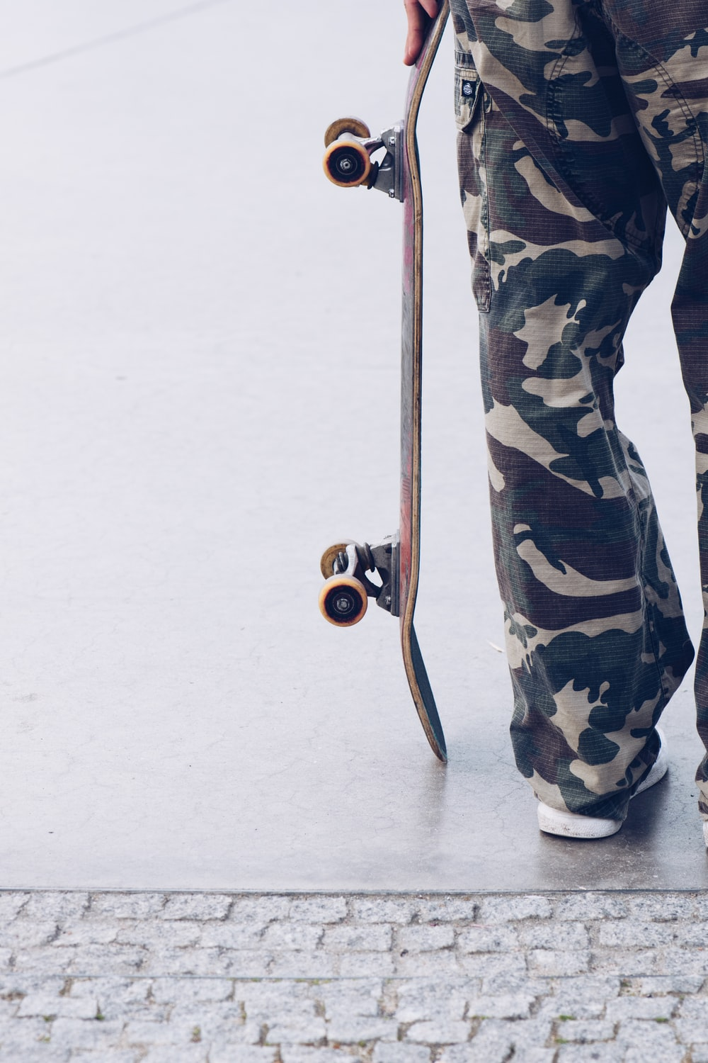 person in green black and white camouflage pants and black shoes holding brown stick