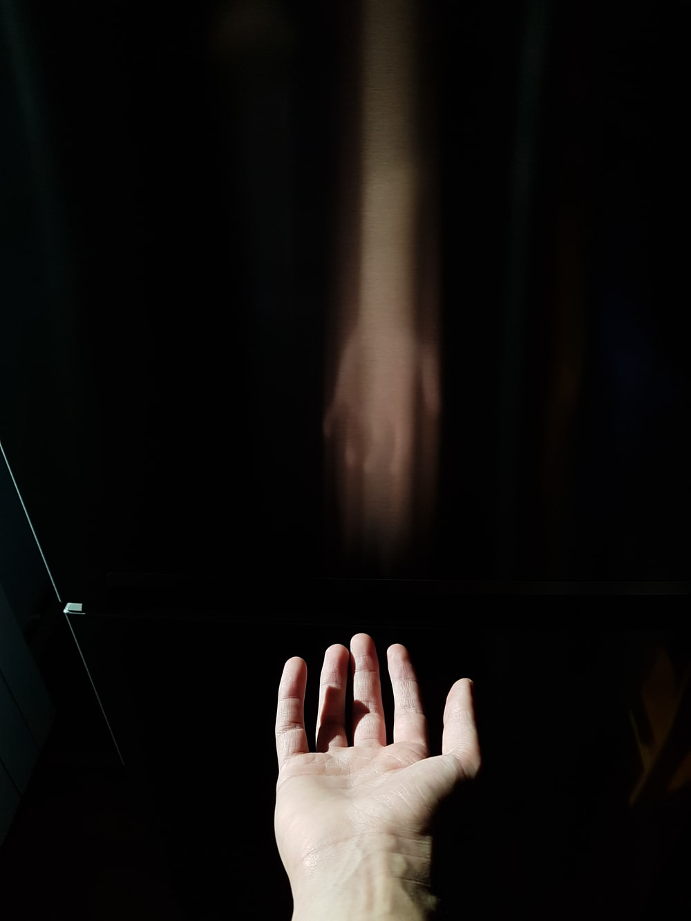 persons hand on black surface