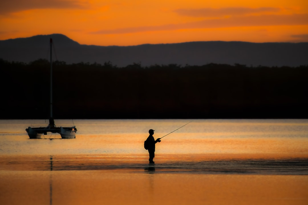 A Fisherman Trying His Luck In the Shallows As the Last Few Minutes of Light Reflect Orange On A Windless Lake. - unsplash