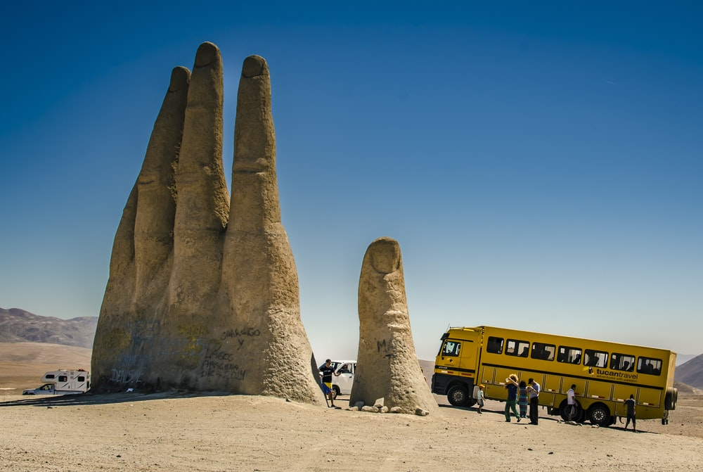 people sitting on brown sand near yellow bus during daytime