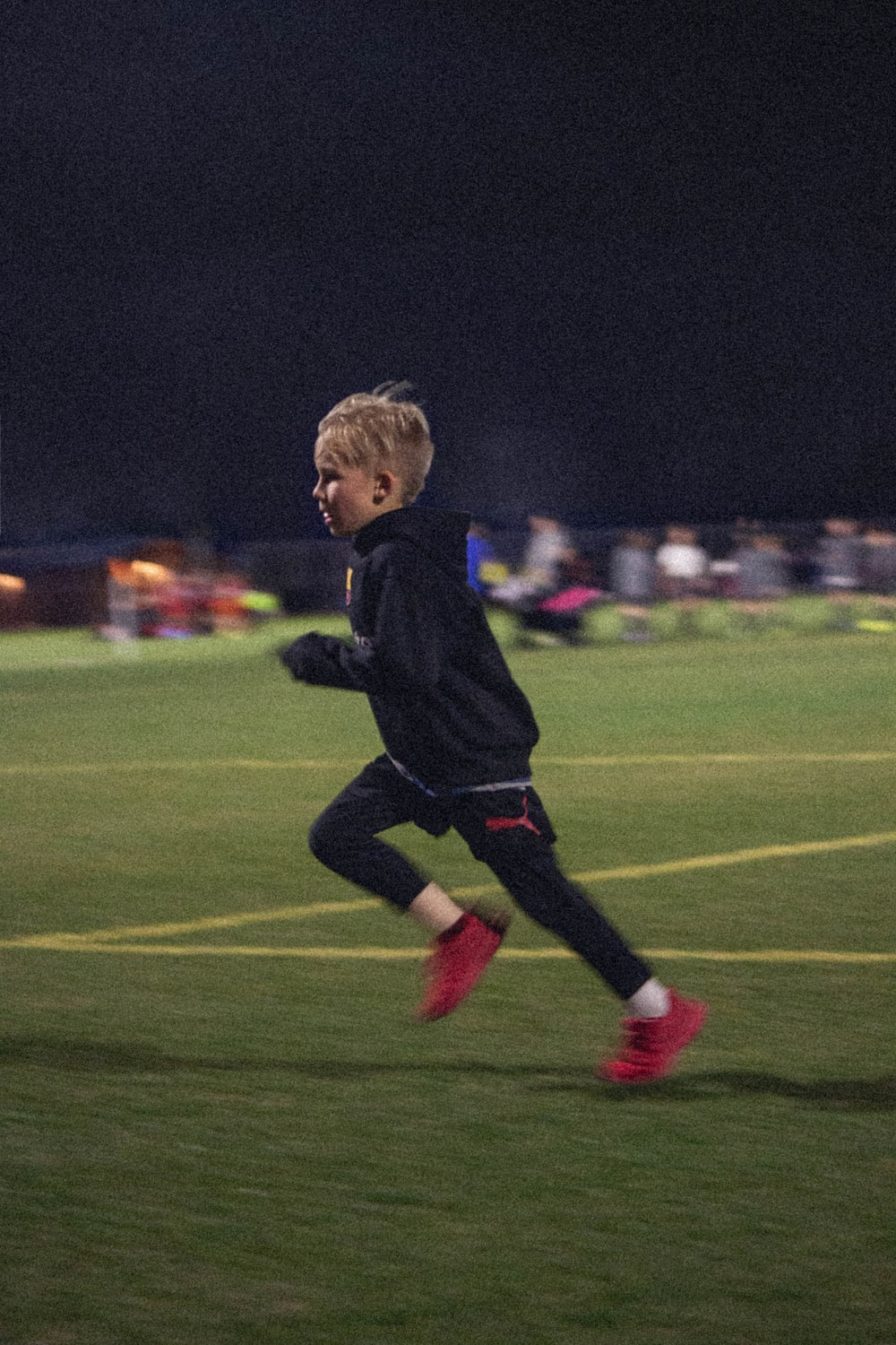 boy in blue long sleeve shirt and black pants running on green grass field during daytime