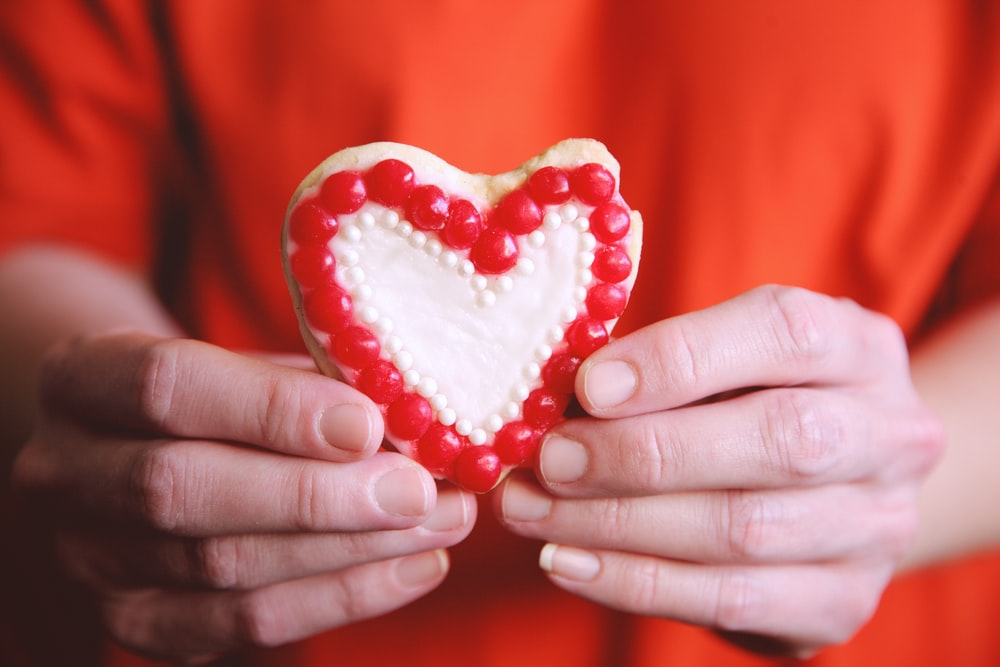person holding heart shaped red heart shaped ornament