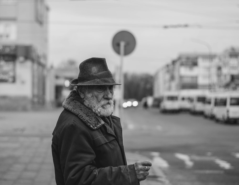 grayscale photo of man in black jacket and hat
