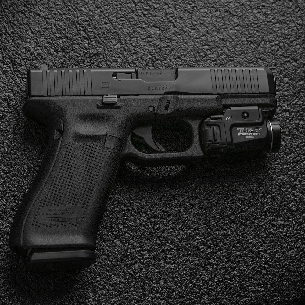 black semi automatic pistol on gray textile