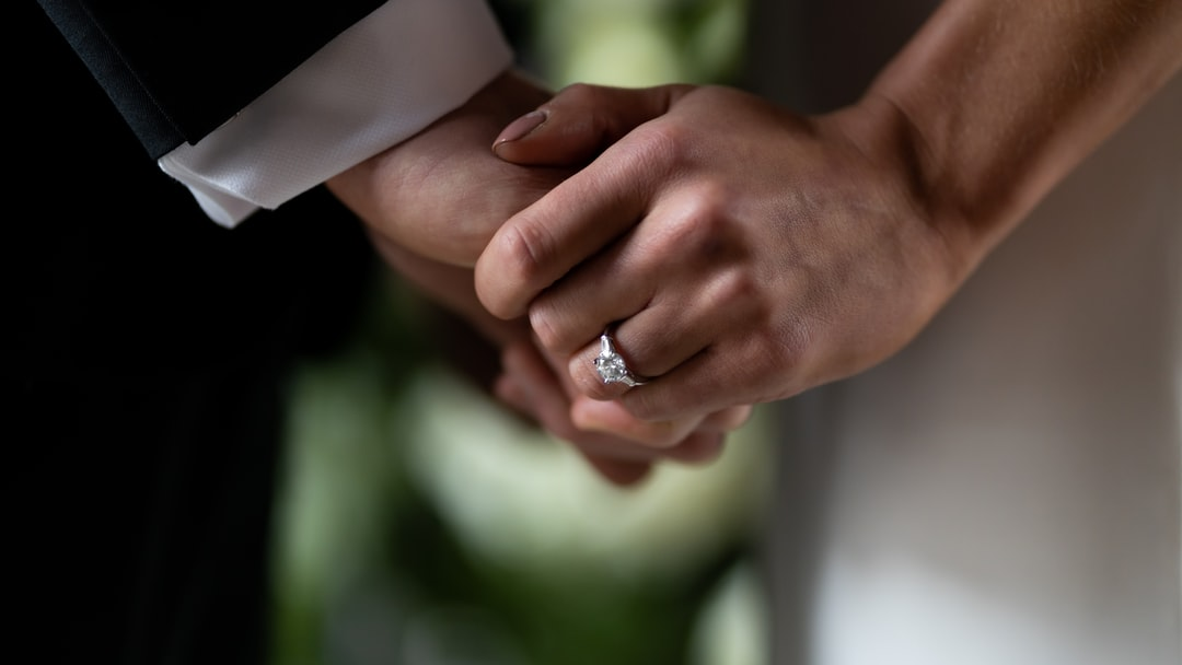 Clasped hands with rings detail shot on wedding day