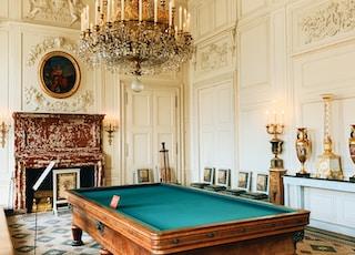 brown wooden billiard table near brown wooden chair