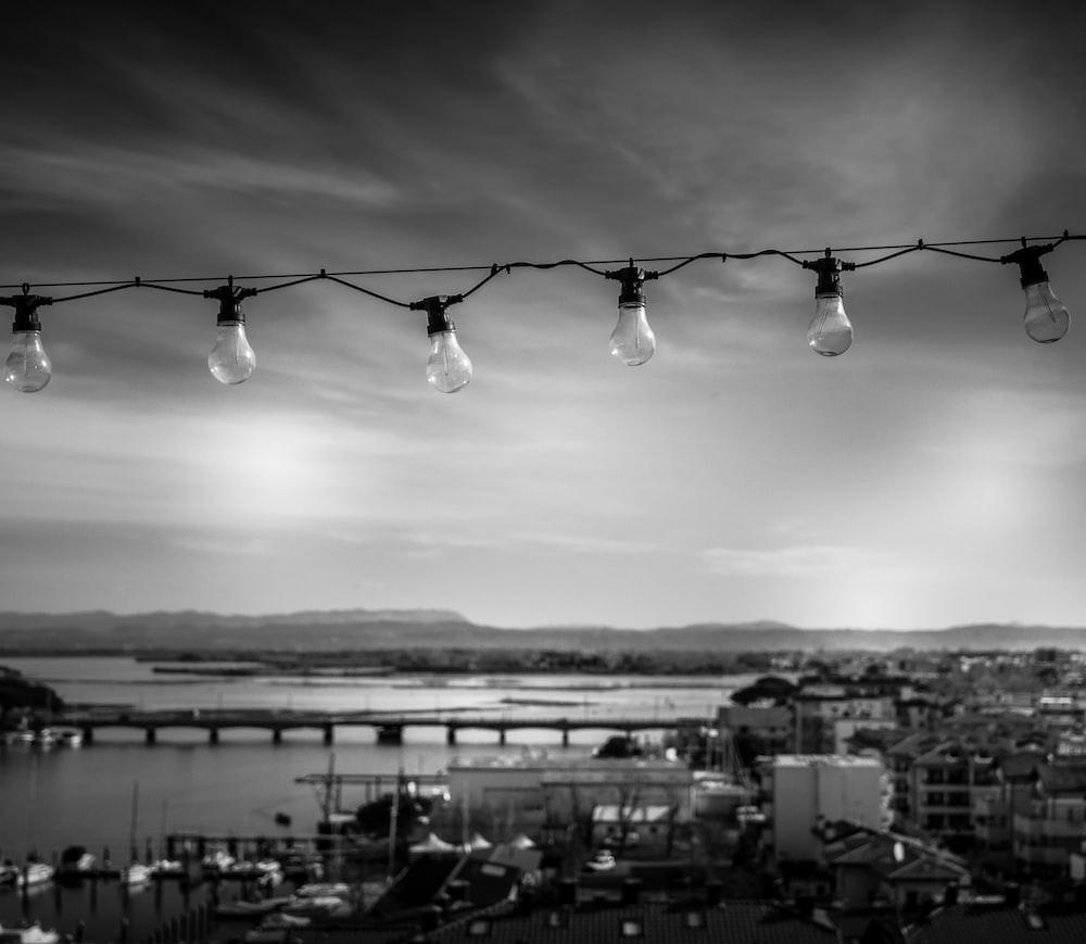 grayscale photo of hanging light bulbs