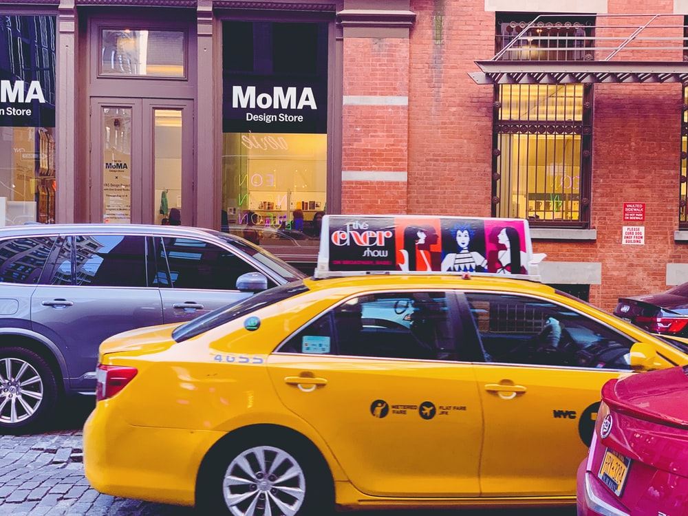 yellow taxi cab parked beside brown brick building during daytime