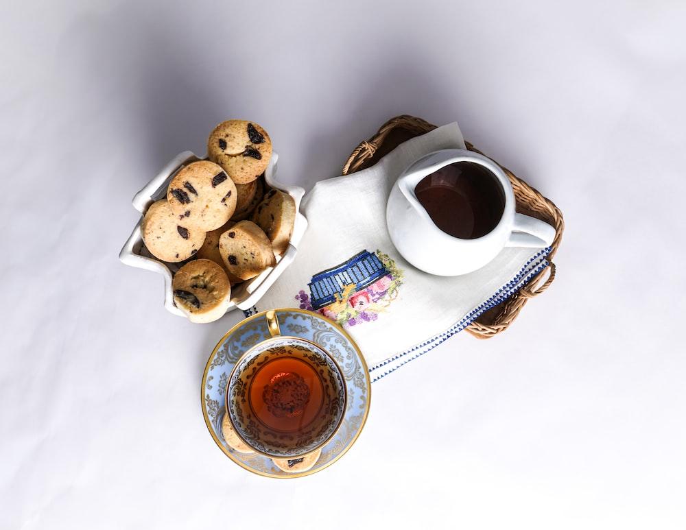 white ceramic mug with coffee beside cookies on white ceramic saucer
