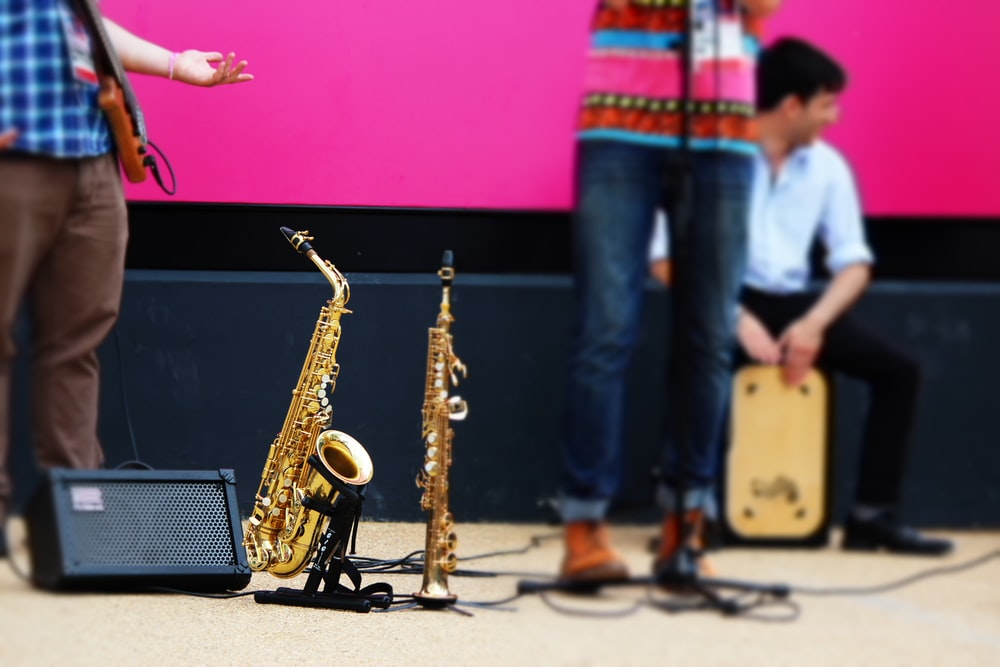 person in blue denim jeans playing saxophone