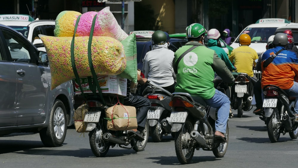 people in green and yellow helmet riding motorcycle during daytime