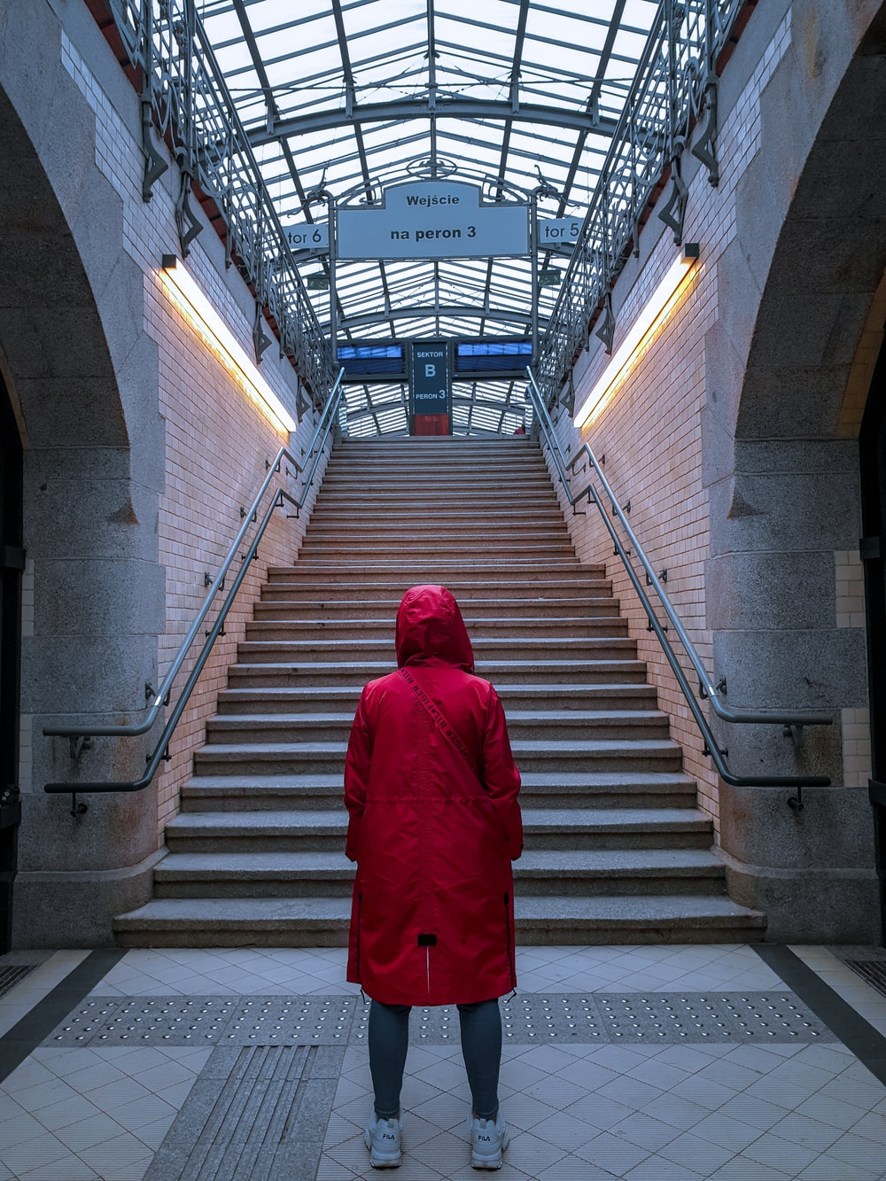 woman in red coat walking on the stairs