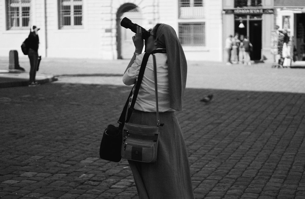 woman in black dress carrying black backpack