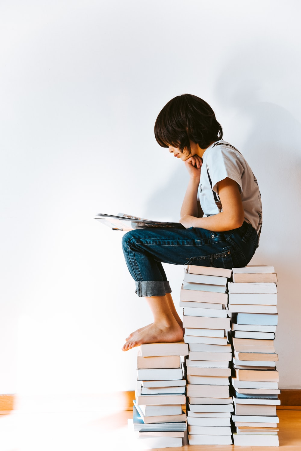 woman in gray t-shirt and blue denim jeans reading book