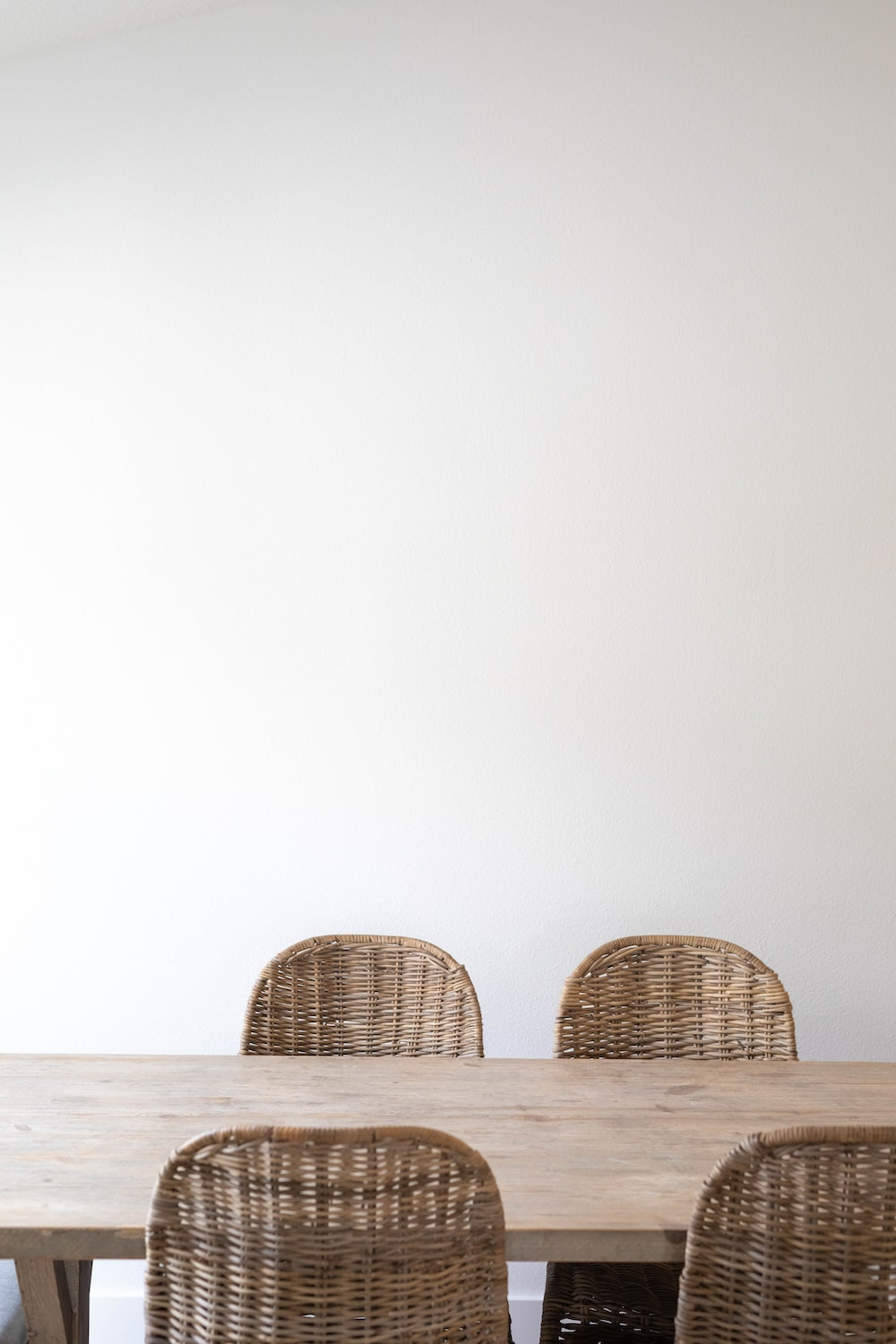brown wicker chairs on white sand