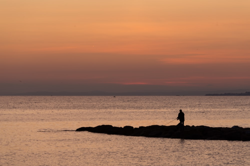 silhouette of person sitting on rock near body of water during sunset