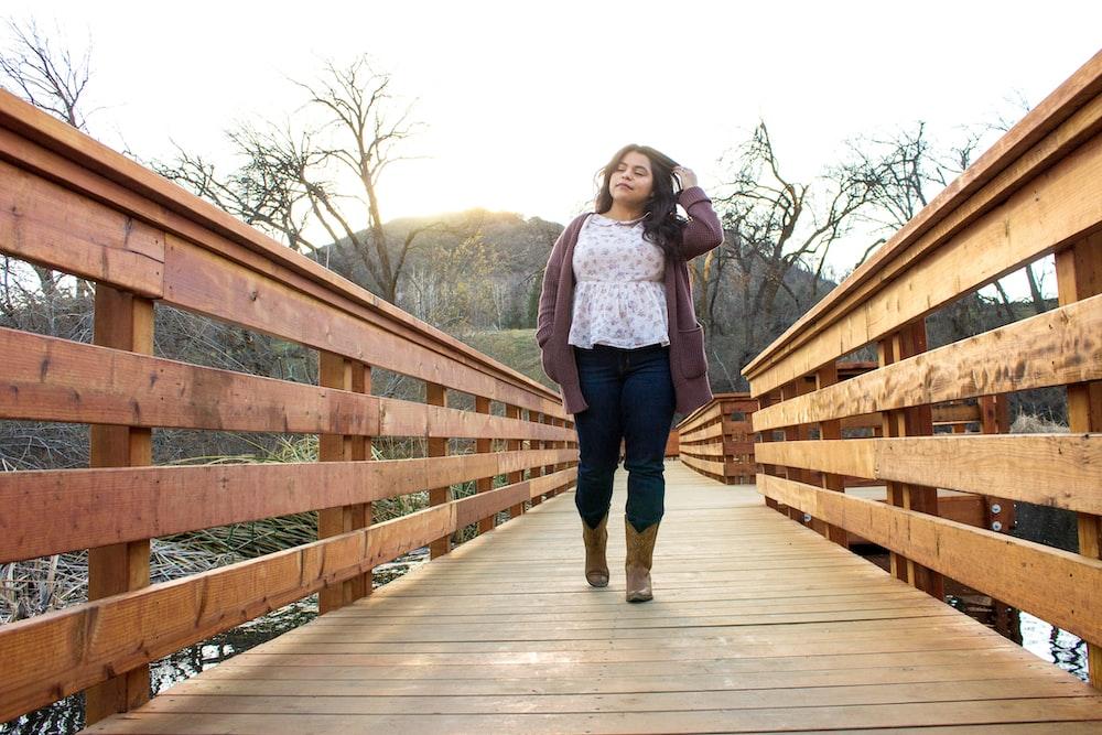 woman in blue denim jacket standing on wooden bridge during daytime