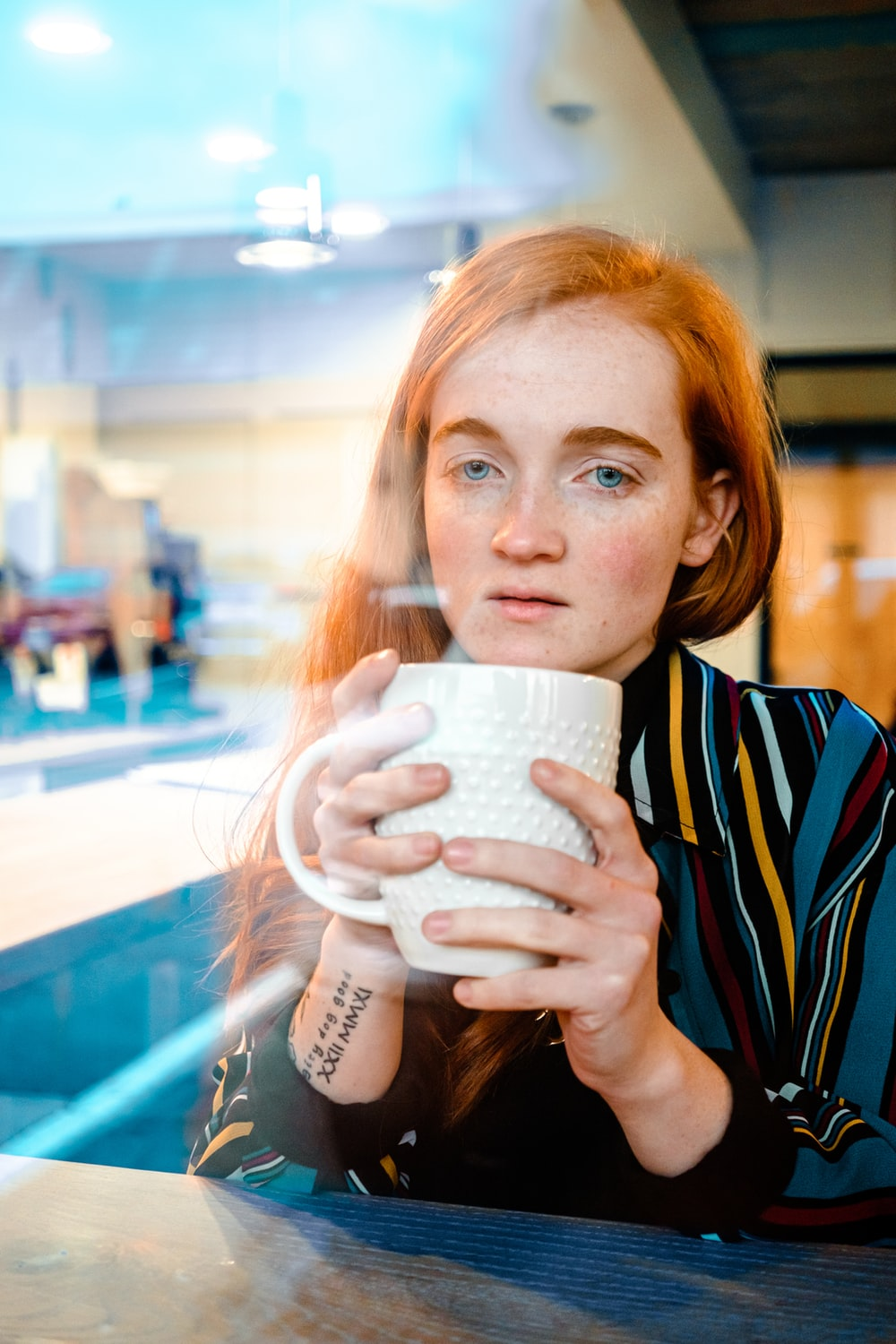 woman in blue and white striped shirt drinking from white ceramic mug