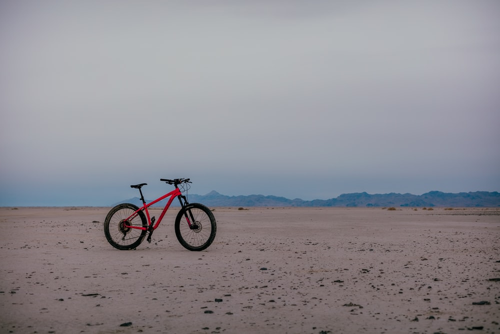 black and red hardtail mountain bike on brown sand during daytime