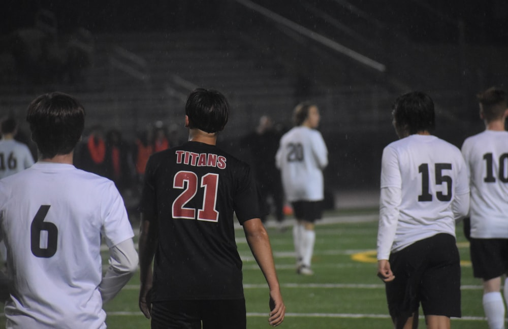 man in black and red jersey shirt standing beside man in white long sleeve shirt