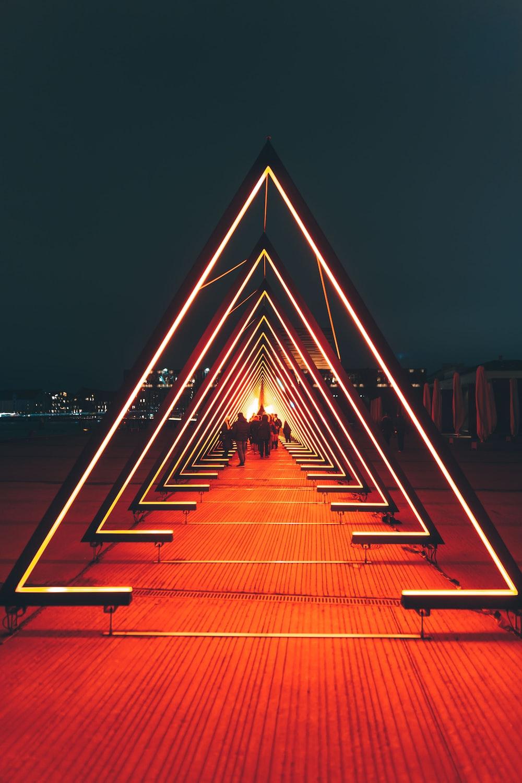 man in black jacket walking on brown wooden pathway during night time